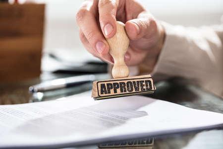 Primer plano de una persona que sostiene el sello aprobado en el documento sobre el escritorio en la oficina Foto de archivo