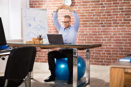 Close-up van een gelukkig zakenman ontspannen op fitness bal in het kantoor Stockfoto - 81652835