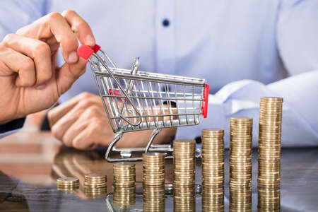 Stack Of Increasing Coins In Front Of The Businessman Holding Shopping Trolley On Desk Standard-Bild