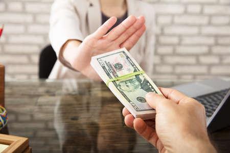 Bijgesneden hand van zakenvrouw weigeren om steekpenningen te nemen van partner op de werkplek