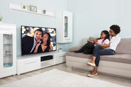 Smiling African Mother And Daughter Having Fun While Watching Television At Home