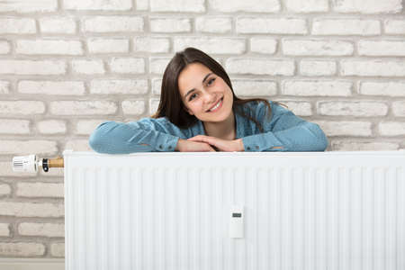Portrait Of A Smiling Woman Behind The Heating Radiator Stock Photo