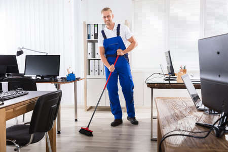 Smiling Male Janitor Cleaning Floor With Broom In Office Stock Photo