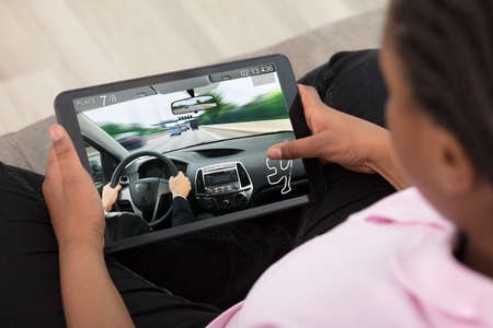Elevated View Of A Girl Playing Car Race Game On Digital Tablet