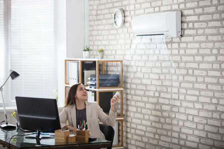 cool gadget: Young Businesswoman Operating Air Conditioner With Remote Controller In Office