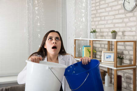 Worried Woman Holding Two Buckets While Water Droplets Leaking From Ceiling Imagens