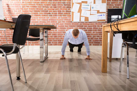 Businessman Doing Push Up At His Workplace