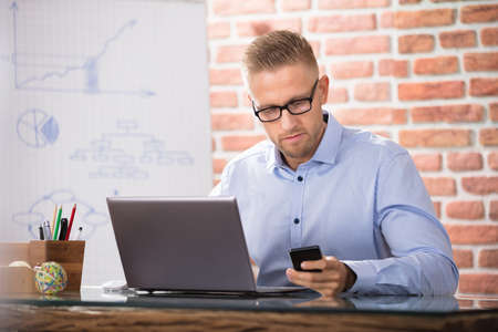 Businessman With Eyeglasses Using Smart Phone While Working In The Office Stock Photo