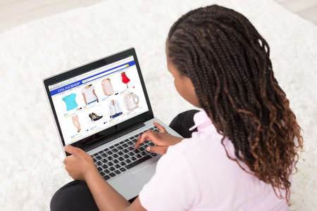 African Girl Sitting On White Carpet Doing Online Shopping Using Laptop At Home photo