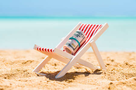 Rolled Up Bundle Of Fifty Dollar Banknotes On Miniature Deck Chair At Beach Foto de archivo