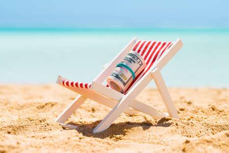 Zwinięte pakiet pięćdziesiąt banknotów dolarowych na miniaturowe krzesło na plaży