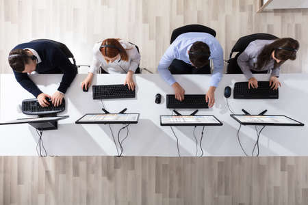 Elevated View Of Call Center Operator Team With Headset Working In Office Banque d'images