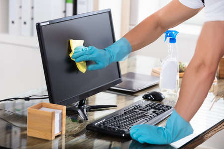 Close-up Of A Janitor's Hand Wearing Gloves Cleaning Computer Screen With Rag Stockfoto