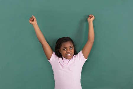 Happy African Girl Raising Her Hand Standing In Front Of Green Chalkboard