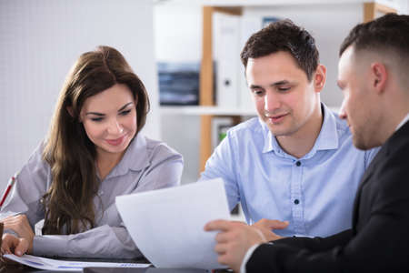 Couple Talking With Advisor During Meeting In Office Stockfoto