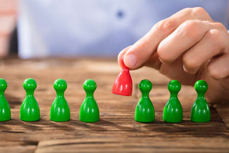 Close-up Of A Person Placing Red Figures In The Green Row Over The Wooden Desk Stock Photo