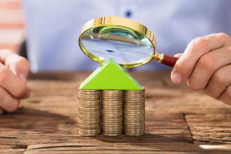 Nahaufnahme einer Person, die Lupe über dem Haus gemacht mit Münzen-Stapel hält