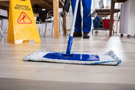 Janitor Cleaning Floor In Front Of Yellow Caution Wet Floor Sign