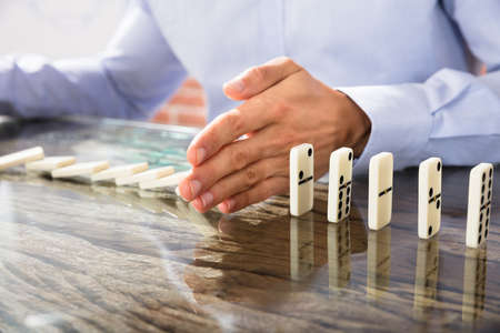 Close-up Of A Businessman Stopping Dominoes Row From Crumbling Over The Glass Desk Stock Photo