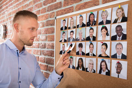 Businessman Selecting Candidates Photo Attached On Corkboard In Office photo