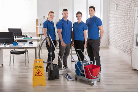 Portrait Of Smiling Janitors With Cleaning Equipments And Caution Sign In The Office