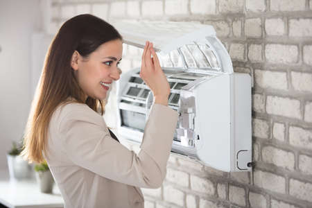 mounted: Young Woman Opening Air Conditioner Attached On Wall