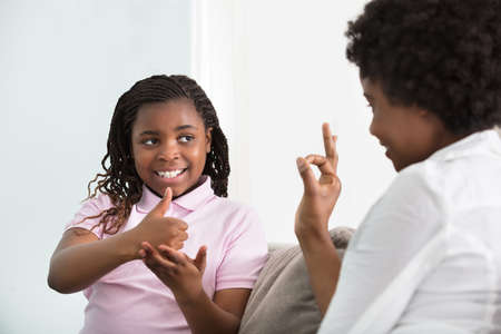 Smiling Young Mother Learning Sign Language To Talk With Her Hearing Impairment Daughter