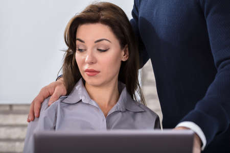 A Boss Touching The Shoulder Of Female Colleague In Workplace At Office Banco de Imagens
