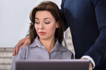 Een baas die de schouder van de vrouwelijke collega raakt op de werkplek op kantoor Stockfoto
