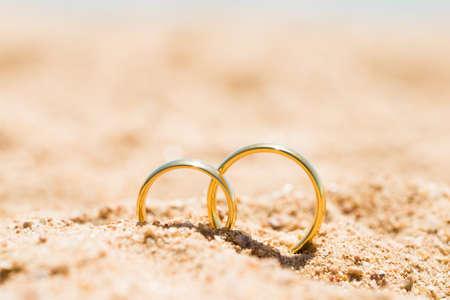 Twee gouden ringen in zand op het strand Stockfoto - 82027287