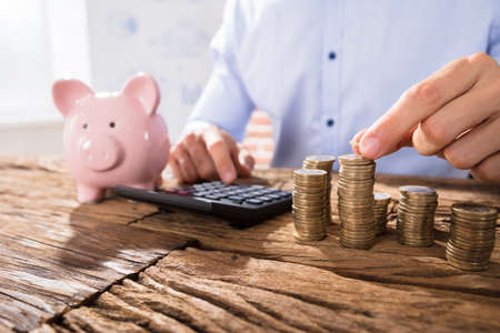 Close-up Of A Business Person Counting Coins Using Calculator With Pink Piggybank Over The Desk Stock Photo