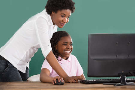 Teacher And Student Looking At Computer In Classroom Against Green Chalkboard Stockfoto