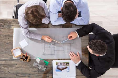 カップルと青写真に取り組んでいる建築家の立面図