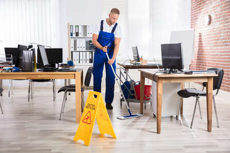 Male Janitor Cleaning Floor With Caution Wet Floor Sign In Office