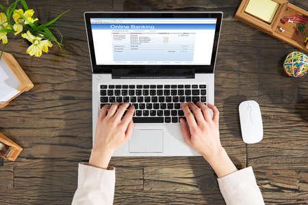 Onderneemster die Online Bankwezen doen die Laptop op Houten Bureau met behulp van