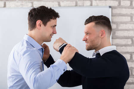 Close-up Of Aggressive Businessman Fighting With His Coworker In Office Stock Photo