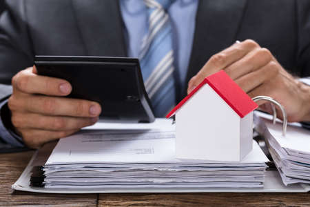 Midsection of businessman calculating invoice with model home on documents at table Imagens