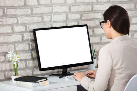 Rear View Of A Businesswoman Working On Blank White Screen Computer In Office