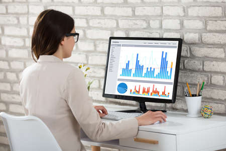 Rear View Of A Businesswoman Analyzing Graph On Computer In Office