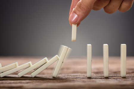 Bebouwd beeld van zakenman het plukken dominostuk die op houten lijst vallen