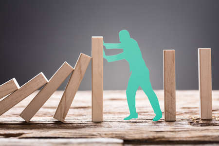 Closeup of green paper man stopping wooden domino blocks on table against gray background Stockfoto
