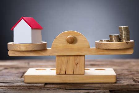 Closeup di modello di casa e monete di bilanciamento su scala di pesatura in legno Archivio Fotografico - 82090332