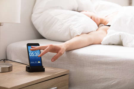 Woman Sleeping On Bed Snoozing Alarm On Smart Phone Screen