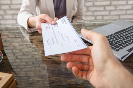 Close-up Of A Business Woman Giving Cheque To Her Colleague At Workplace In Office Stockfoto