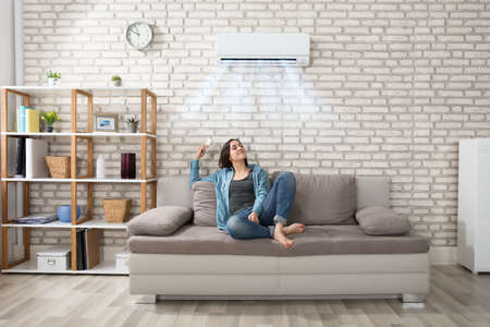 Happy Young Woman Holding Remote Control Relaxing Under The Air Conditioner Foto de archivo
