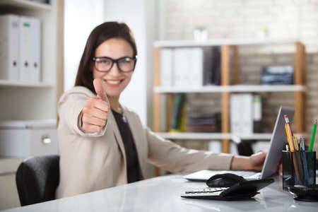 Portrait Of A Smiling Young Businesswoman Showing Thumbs Up Foto de archivo