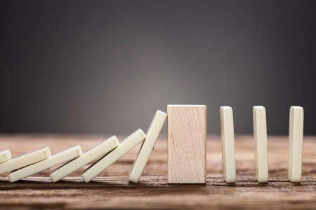 Close-up van houten blok in het midden van dalende en rechte dominostukken op lijst tegen grijze achtergrond