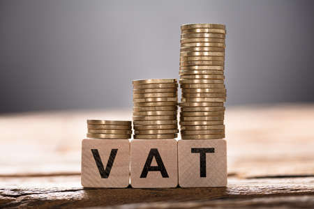 Closeup of VAT text written on wooden blocks with stacked coins Stock Photo