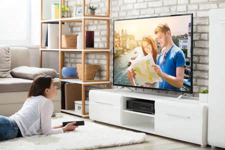 집에서 텔레비전을보고 즐기는 카펫에 누워있는 젊은 여자 스톡 콘텐츠