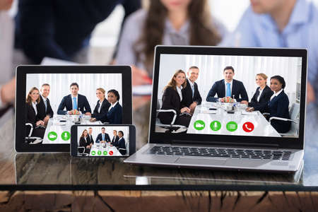 Video Conferencing On Modern Electronic Devices Over The Office Desk Stock Photo